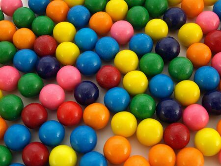 A colorful variety of gumballs spilled out on a white background.