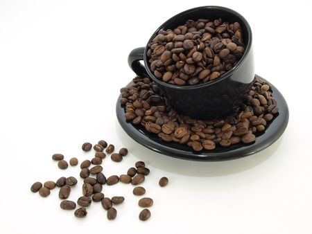 A black cup and saucer filled to spilling with roasted Columbian blend coffee beans. Isolated over white. Stock Photo