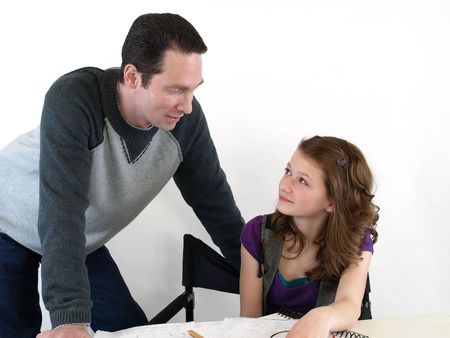 A father helps his daughter with her school homework. Over white.