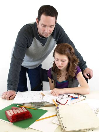 conferring: A father helps his daughter with her school homework. Over white.
