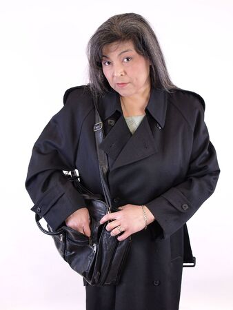 A Hispanic female reaches into the front pocket of her briefcase. Over white. Stock Photo