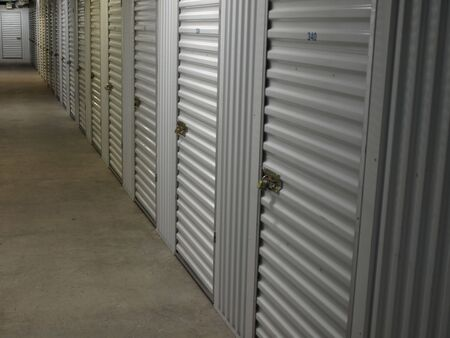 A row of interior self storage locker doors. Interior shot, natural lighting.