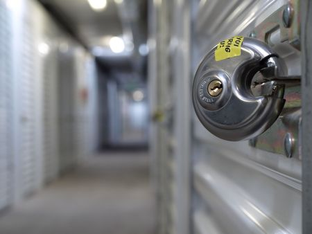 A steel padlock clipped to a storage unit door. Limited focal range to emphasize the lock. Stock Photo