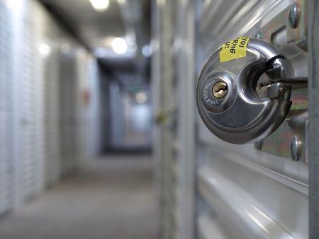 Ein Stahl Vorhängeschloss abgeschnitten, damit er eine Speicher-Einheit-Tür. Begrenzte Brennweitenbereich, die Sperre zu betonen.