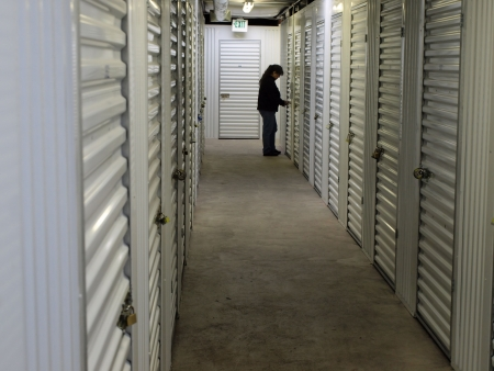 A woman stands at the end of a row of self storage lockers, opening a lock. Interior shot.