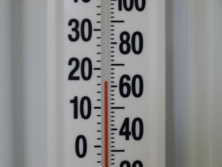 Close up of a wall thermometer. Temperature reads 17 degrees Celsius, 62 degrees Fahrenheit. Stock Photo
