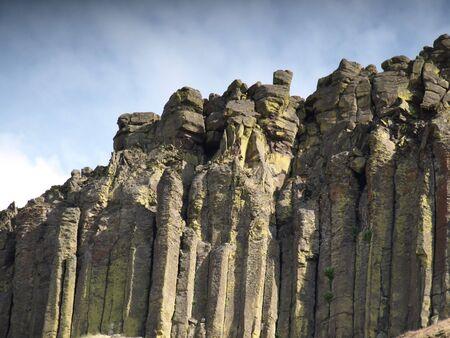 monta�as caricatura: Un acantilado rocoso, alto alcanza hacia el cielo, enormes monolitos de piedras proteger todo lo que se encuentra detr�s y debajo de ellos. Por el lado de las rocas, en pie como una multitud, viendo de caras.