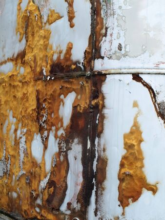 A painted white metal structure starts to rust and corrode over time, orange and yellowed rust stains on the side. Background texture image.