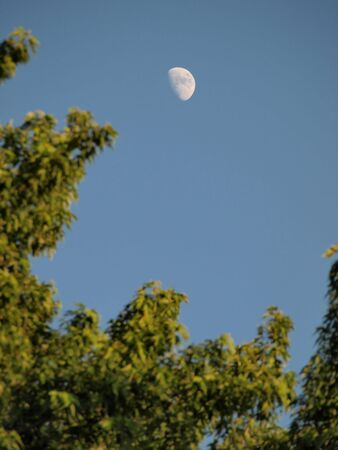 A half moon appears in the afternoon sky, awaiting its evening appearance. Stock Photo