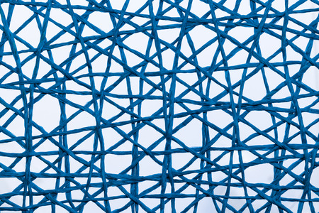 Blue string crossing over each other to make a net or web.