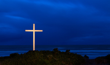 White cross at a beach as a dark storm comes over.