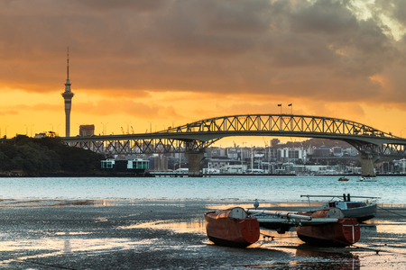 Auckland Harbour at low tidy with a sunrise sky.
