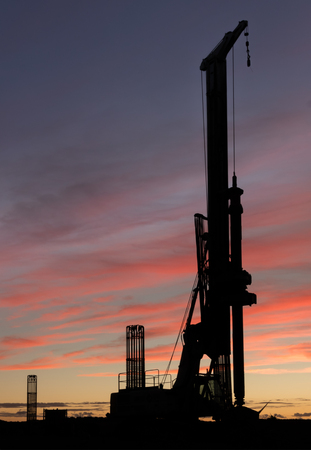 Large construction Drill with a sunset Sky.