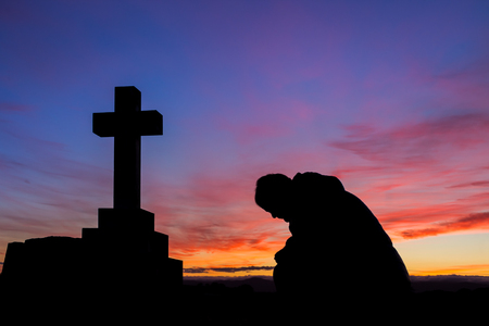 Mand in prayer by a cross at first light of the day. Stock Photo