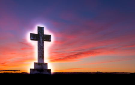 Stone cross with a glow around it, on a hill area with a wonderful dawn morning sky.
