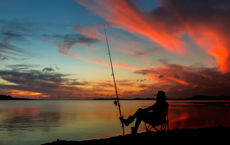 Made sitting by his fishing rod at sunset. Stock Photo