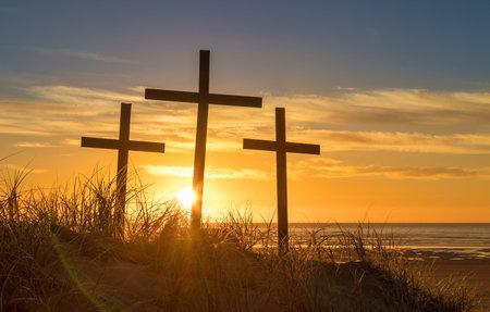 夕日として砂の丘の上に3つの十字架。