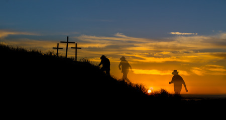 Cowboy hated man walking to three cross hill as the sunsets.