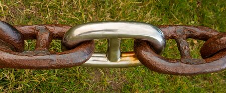 Old rusted link chain with a new stainless steel link. Stock Photo