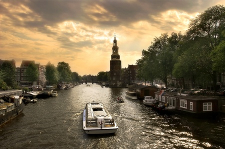 View on city canal (Amstel river) with cruise ship in Amsterdam, Netherlands.