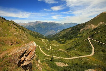 unpaved road: View on unpaved road running through the valley in Alps, Italy.