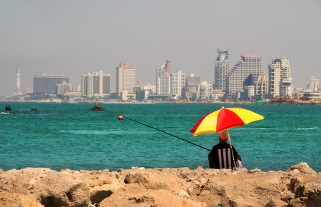 israeli: Fisherman sitting on wavebreaker on Mediterranean Sea and looking at the modern building of Tel-Aviv, Israel. Editorial