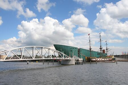 amstel river: Modern bridge over Amstel river and vintage ship standing nearfamous Nemo Building in Amsterdam, Netherlands. Stock Photo