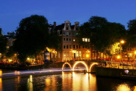 amstel: View on city canal (Amstel river) and small illuminated bridge at evening in Amsterdam, Netherlands (Holland) Stock Photo