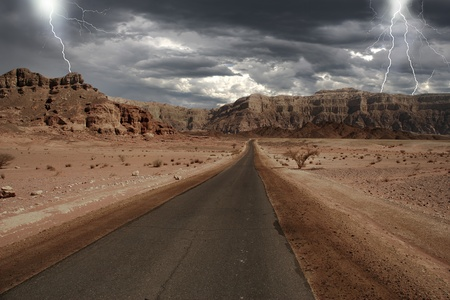 View on narrow road running through the mountains of Arava desert under the cludy stormy sky with lightnings in Israel. photo