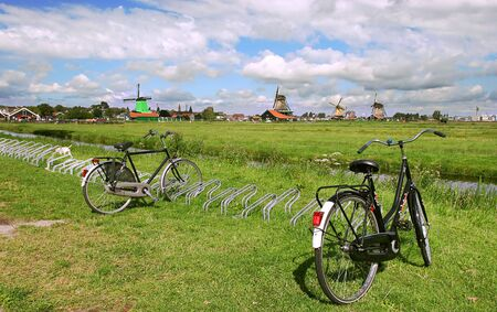 Green fields, creek and windmills in famous Zaanse Schans village near Amsterdam, Netherlands. Stock Photo - 10270044