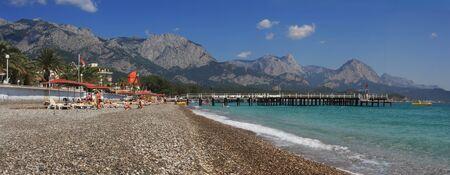 Panoramic view on public beach, Mediterranean Sea and mountains in popular touristic resort Kemer (Antalya), Turkey. Stock Photo