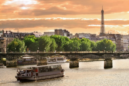 Cruise ship on Seine river move towards bridge and Eifeel Tower. Stock Photo