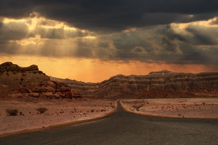israeli: Beautiful cloudy evening sky over narrow road running towards mountains of Arava desert in Israel. Stock Photo