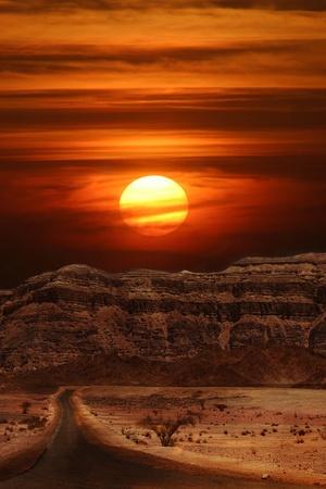 イスラエルで Arava 砂漠の山に沈む夕日の垂直指向のイメージ。 写真素材
