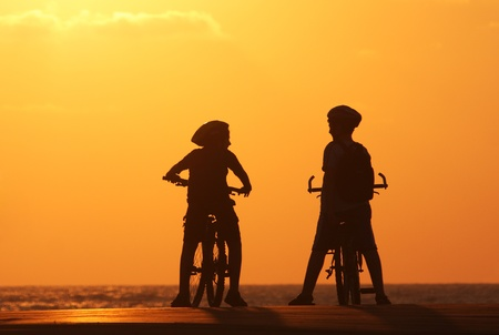 mediterranean sea: Silhouette of two kids on bicycles standing on the pear on Mediterranean Sea at sunset. Stock Photo