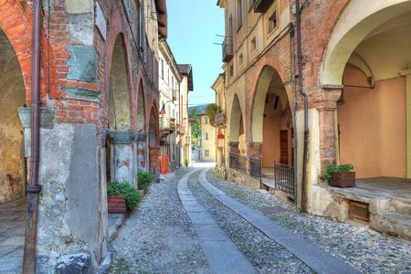 Narrow paved street among vintage brick houses in town of Avigliana, northern Italy.