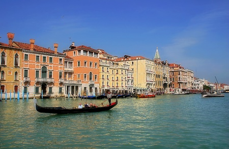 Gondola passing by multicolored buildings along famous Grand Canal in Venice, Italy. Editorial