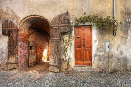 サルッツォ町、北イタリアで古いれんが造りの家でガレージに木製のドアおよびゲート入り口。