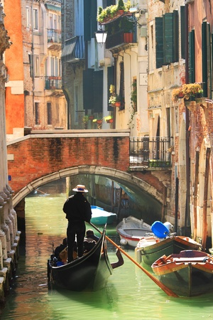 Vertical oriented image of gondola passing on small canal among old historic houses and bridge in Venice, Italy. photo
