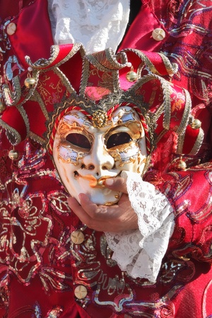 participant: VENICE, ITALY - MARCH 04: Unidentified participant wear traditional costume and holds mask in his hand during famous Venetian Carnival on March 04, 2011 in Venice, Italy.