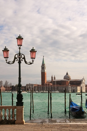 Vertical oriented image of venetian lamppost, gondola on Grand Canal and San Giorgio Maggiore church in Venice, Italy. photo