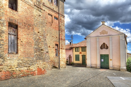 Old brick house and small chapel on narrow paved street in town of Castiglione Falletto, northern Italy.