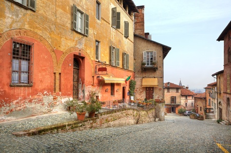 saluzzo: Narrow paved street among vintage multicolored houses in town of Saluzzo, Northern Italy. Stock Photo