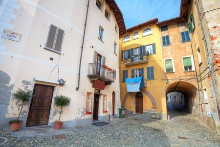 empedrado: Peque�a estrecha calle pavimentada entre las casas multicolores de la ciudad de Saluzzo, Italia del Norte.