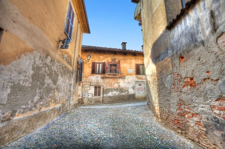 Narrow paved street among vintage multicolored houses in town of Saluzzo, Northern Italy. Stock Photo - 11570535