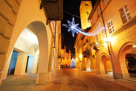 Alba old town central street with illuminations and Christmas Tree against San Lorenzo Cathedral on the background in Italy. Stock Photo - 11748971