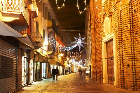 Alba old town central street with opened shops, bars and stores and illuminations for Christmas and New Year holidays.