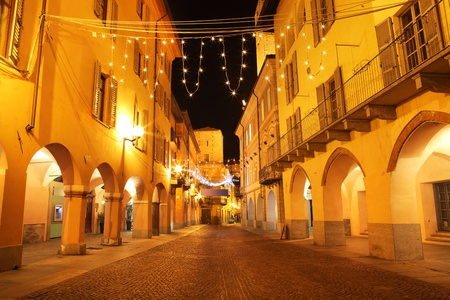 passages: Narrow paved street among old buildings with arch passages and Christmas illuminations in town of Alba, Northern Italy.
