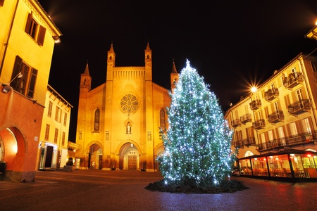 Illuminated Christmas tree on central plaza against San Lorenzo Cathedral in historic part of town of Alba, Italy.