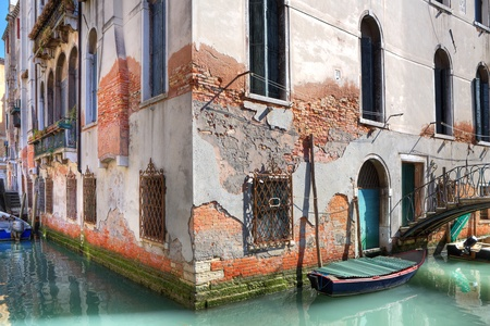 small boat: Ancient brick building on small canal with boats and bridge in Venice, Italy.